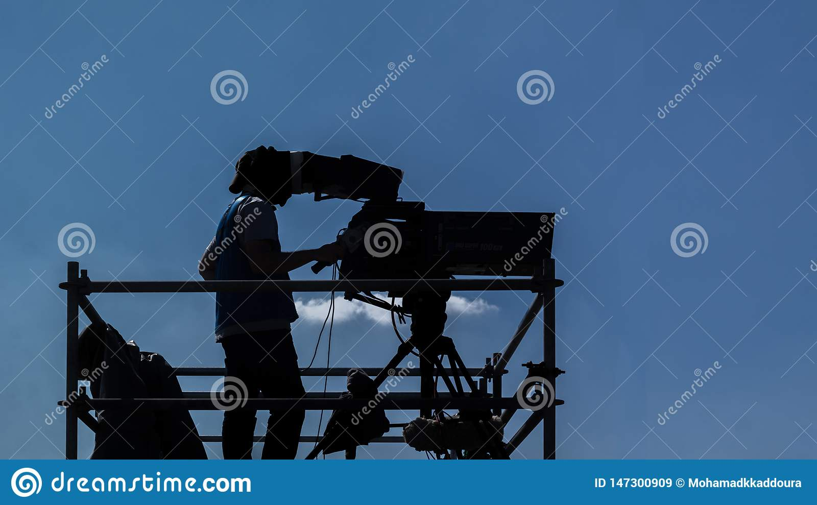 Оператор видеокамеры - человек работая и снимая на наборе с его оборудованием