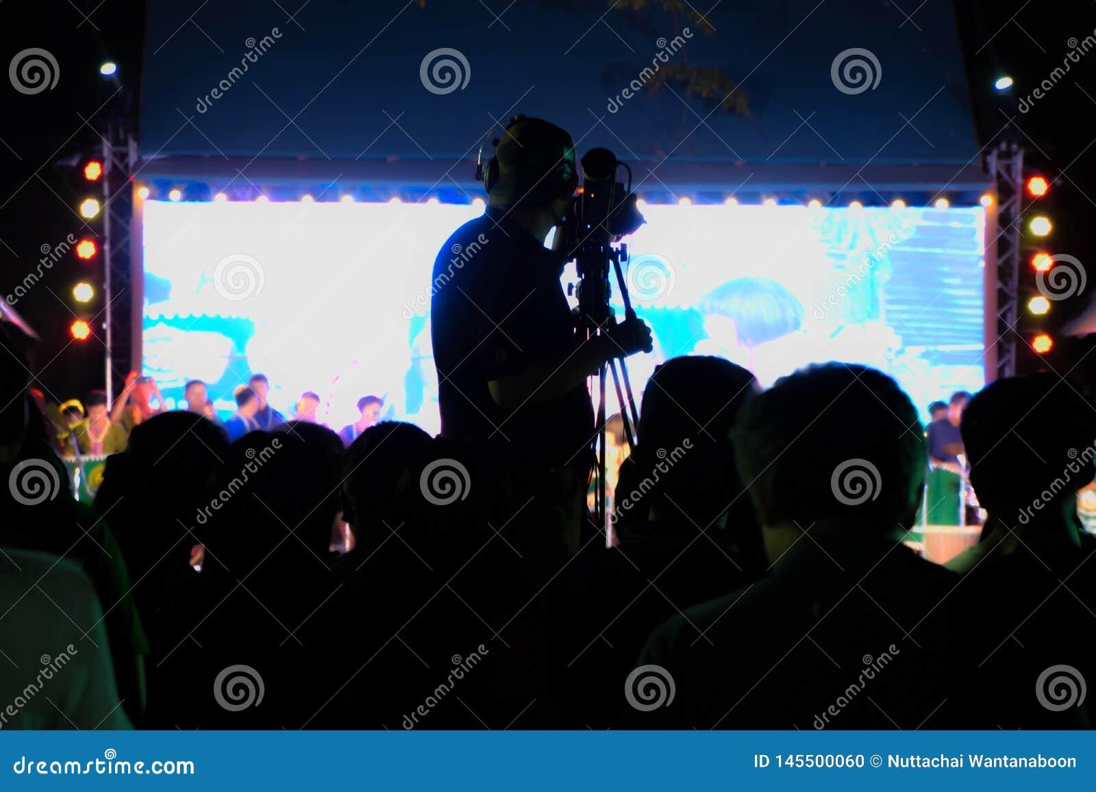 Оператор на работе, силуэте оператора оператора снимая представления в реальном маштабе времени Pong Lang на Бангкоке, Таиланде -