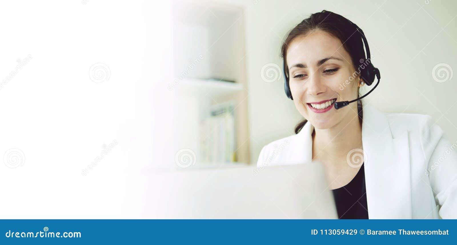 Оператор работы с клиентом женщин счастливый усмехаясь с шлемофоном
