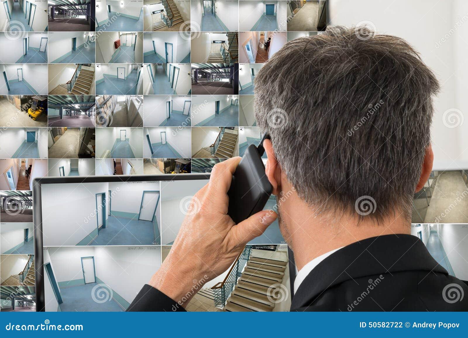 Оператор системы безопасности смотря отснятый видеоматериал cctv