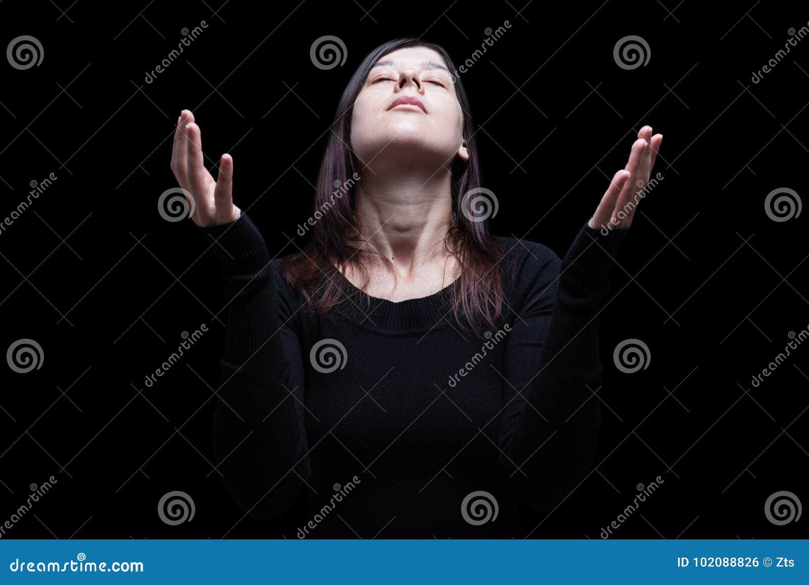 Оплакивая женщина моля, при оружия протягиванные в поклонении к богу