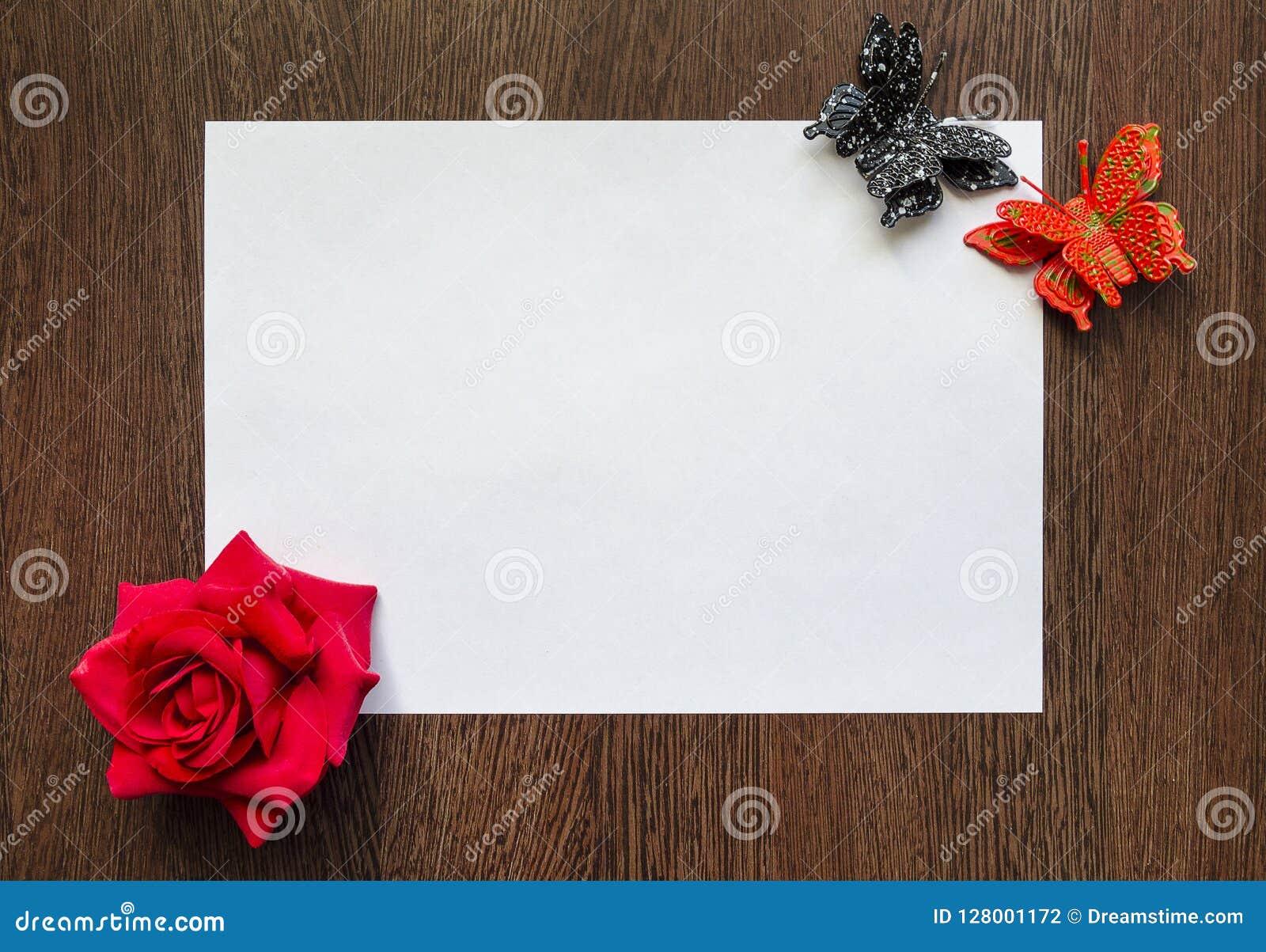 Опорожните белый лист бумаги для вашего текста на темной деревянной предпосылке таблицы Пестротканые цветки и бабочки вокруг его