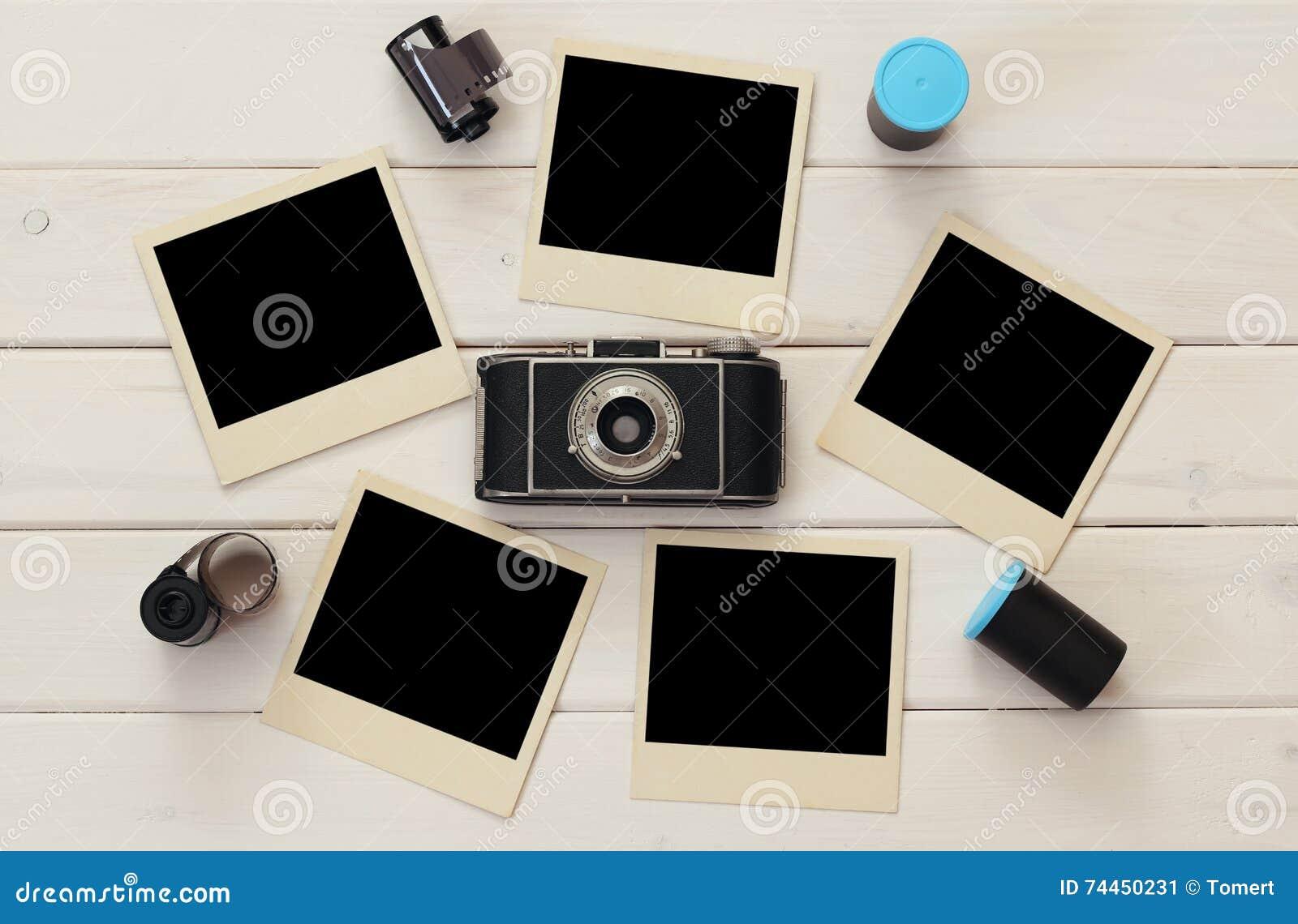 Опорожните немедленные фотоснимки рядом с старыми кренами камеры и фильма