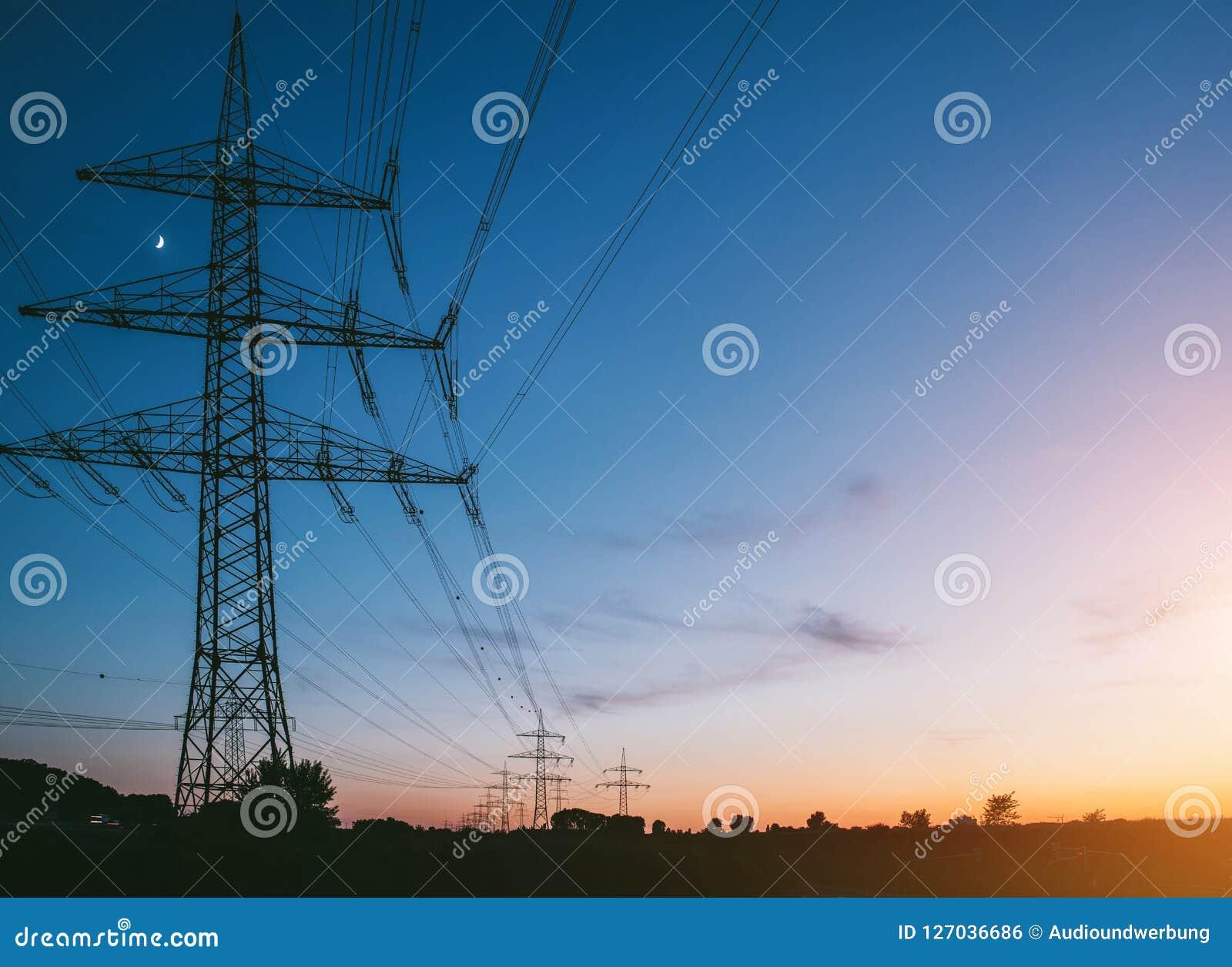 Опоры электричества на заходе солнца транспортируя экологически чистую энергию