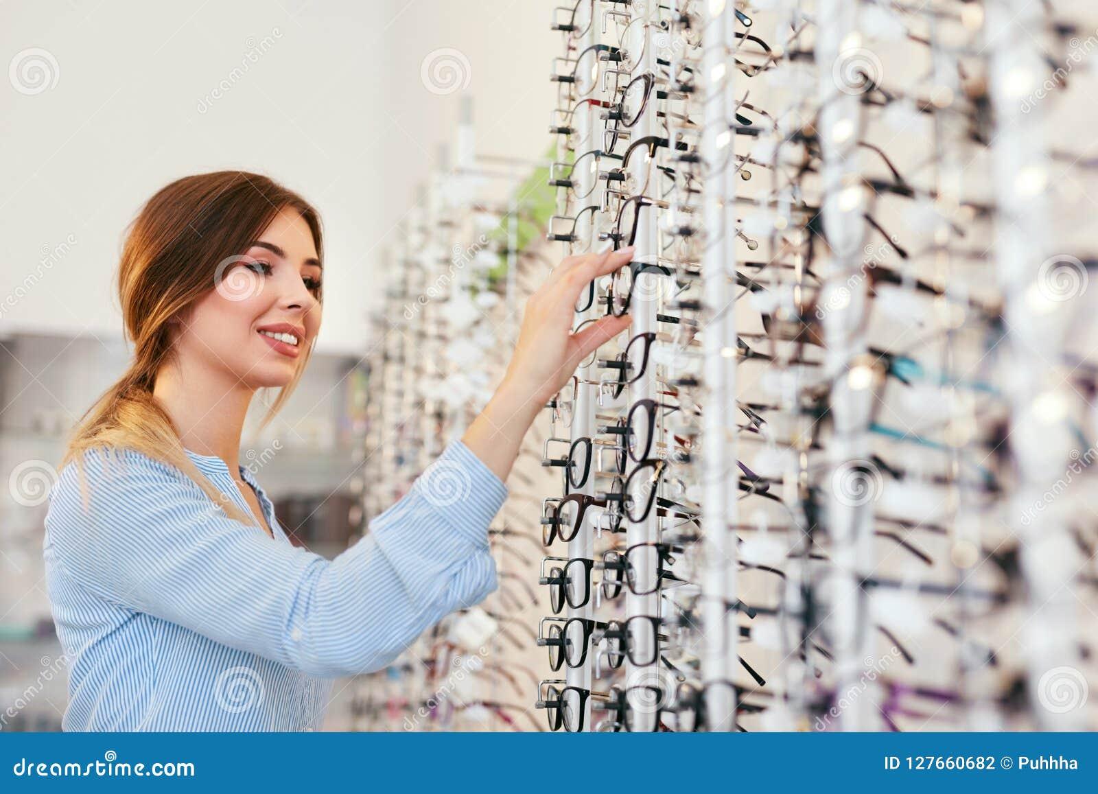 оптически магазин Женщина около витрины ища Eyeglasses
