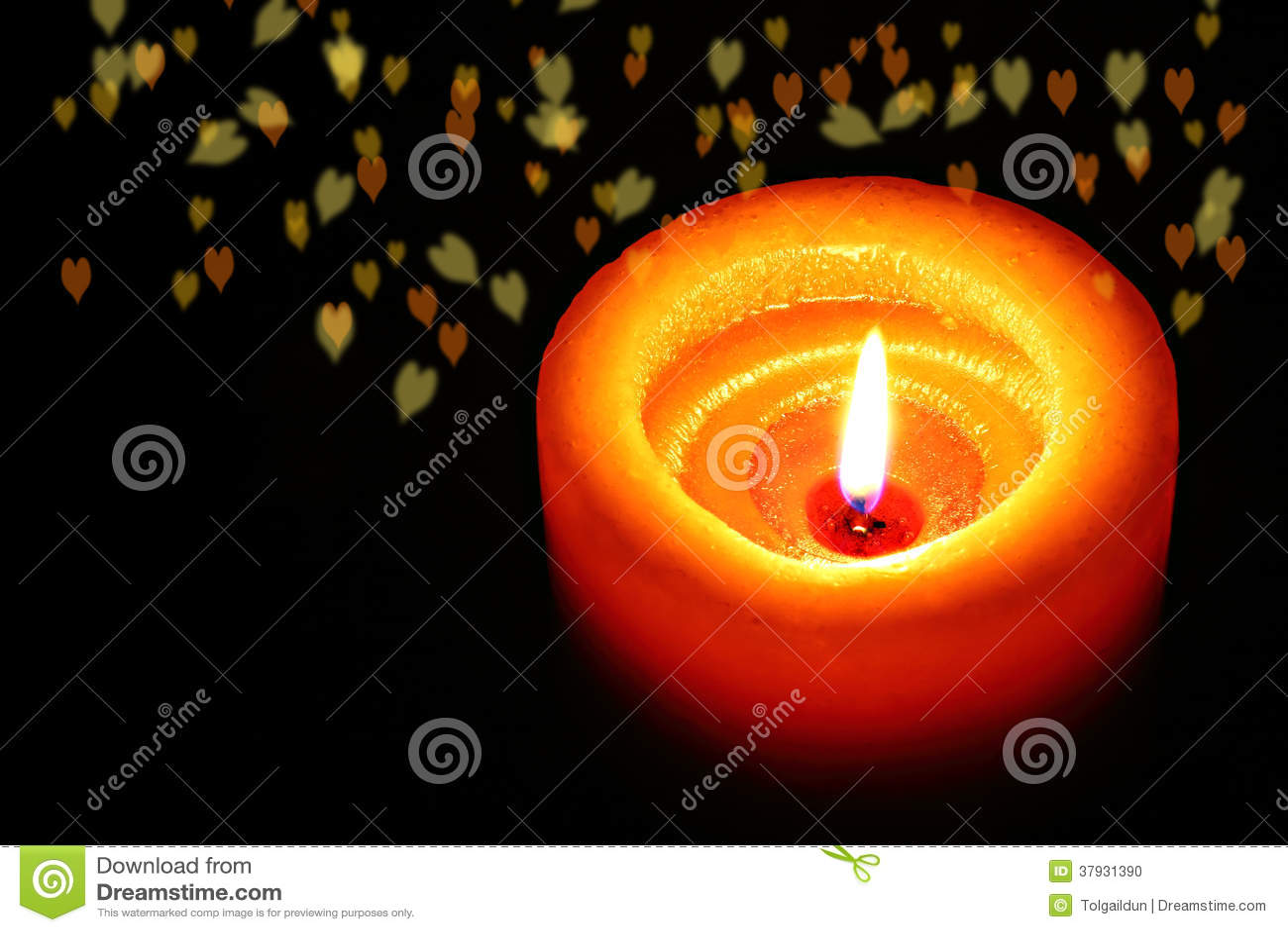 Оранжевая свеча с романтичными сердцами нерезкости