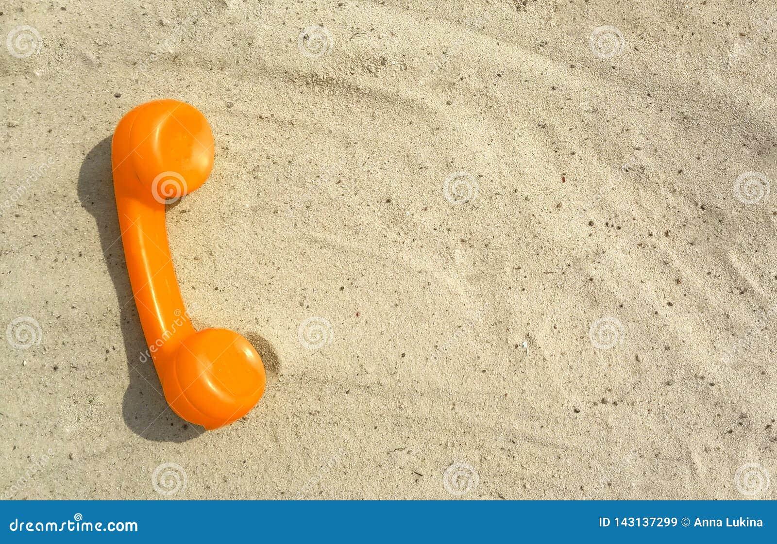 Оранжевая трубка старого винтажного телефона лежит на песке