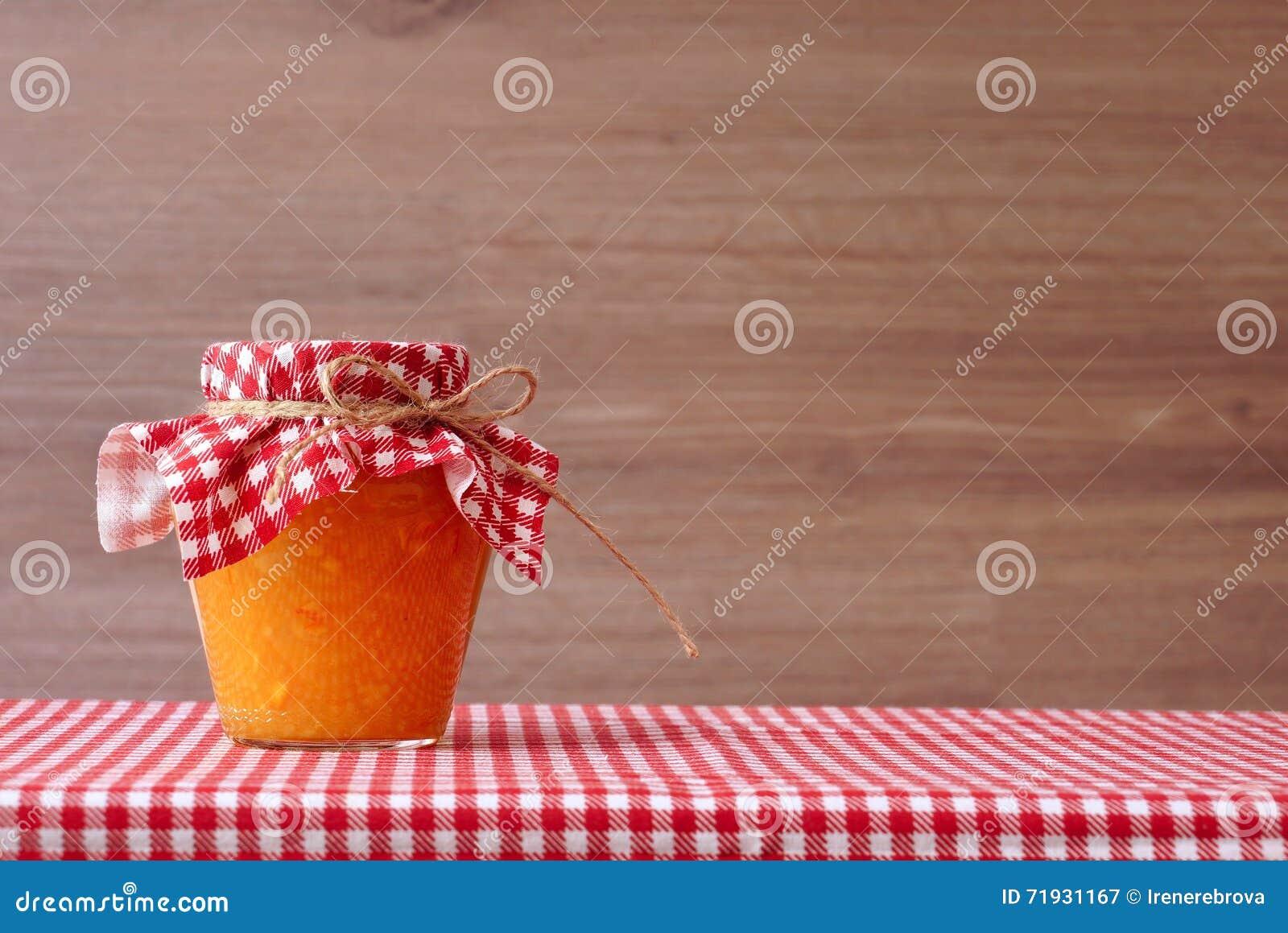 Оранжевое варенье в стеклянном опарнике на красной checkered скатерти