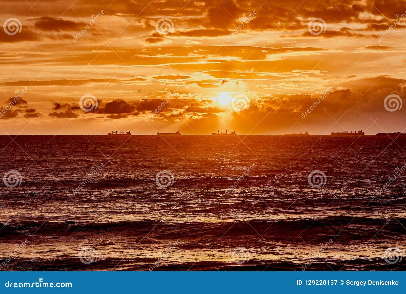 Оранжевое солнце с облаками над серым морем с волнами Волшебный заход солнца на Чёрном море в Gelendzhik Изумительная естественна