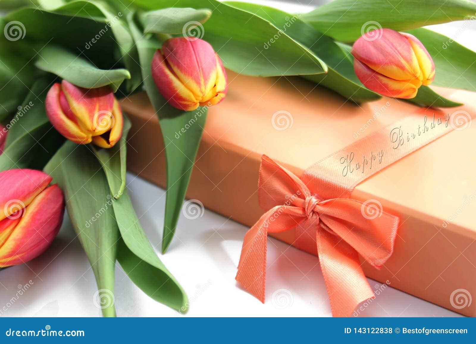Оранжевые желтые тюльпаны, подарочная коробка и текст с днем рождений на петле