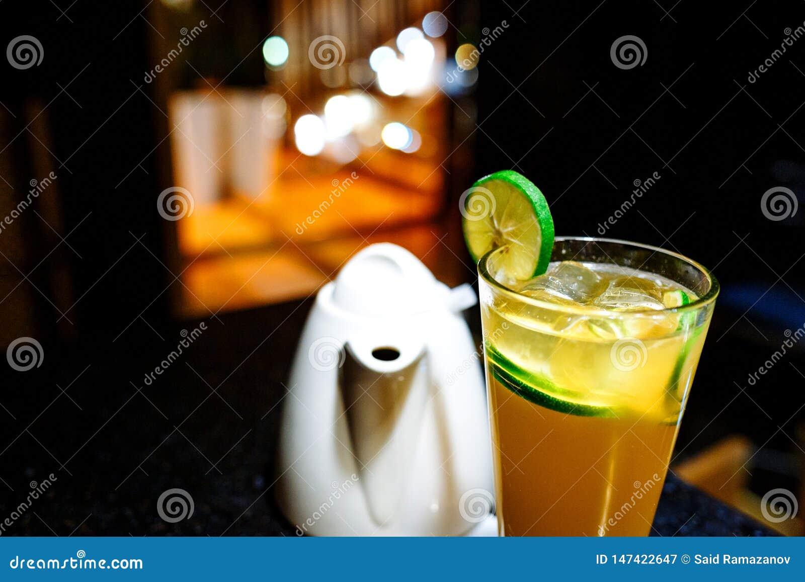 Оранжевый коктейль с известкой и чайником на темной предпосылке