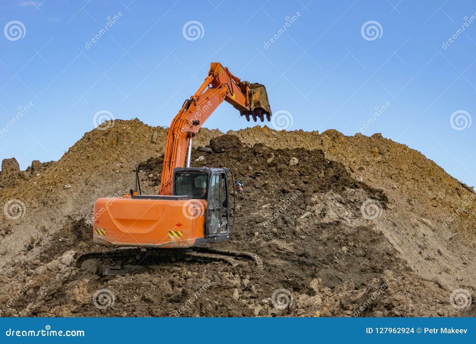 Оранжевый экскаватор на куче песка с поднятым ведром