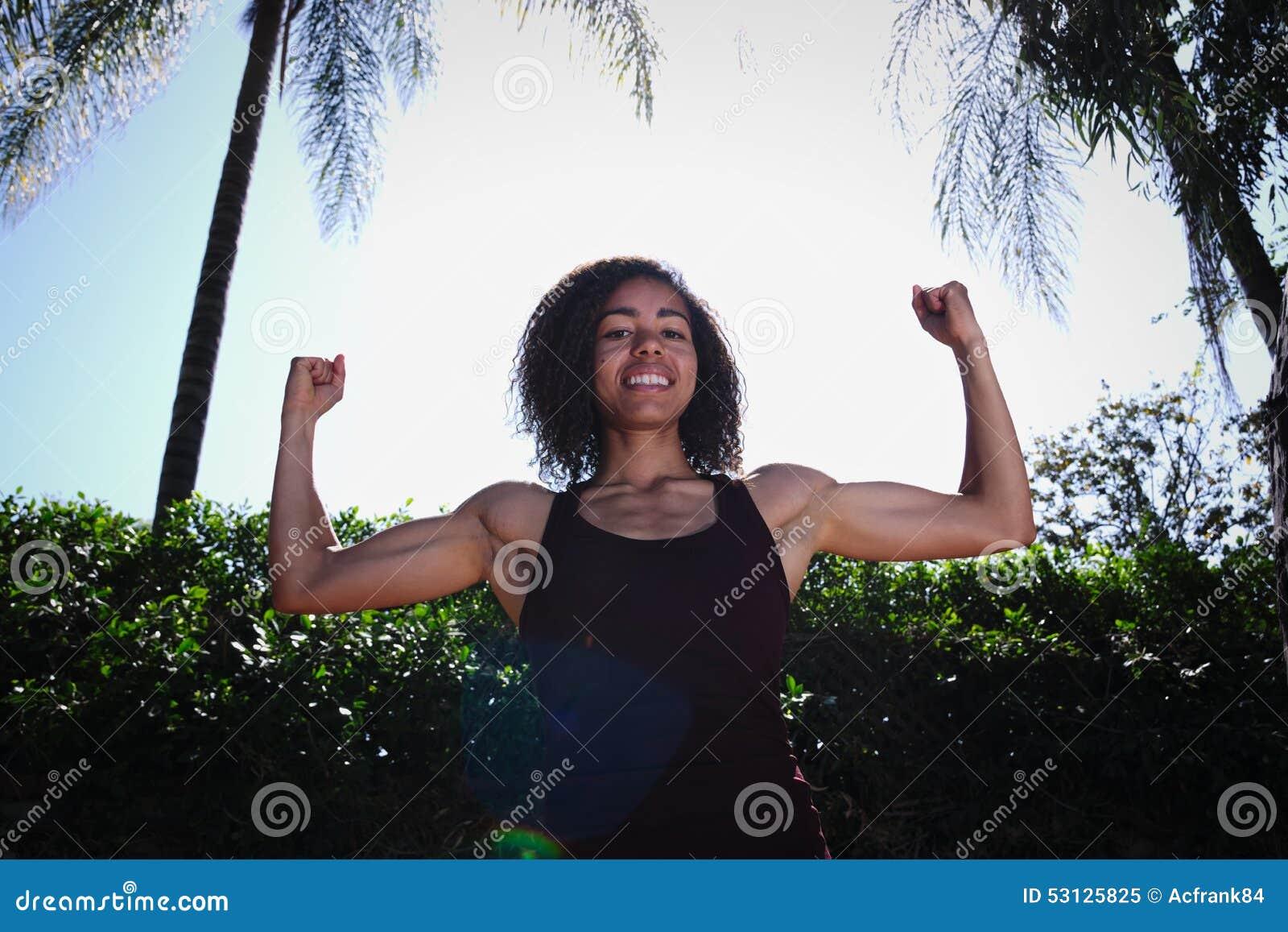 Оружия сильной молодой женщины завивая для того чтобы показать бицепс
