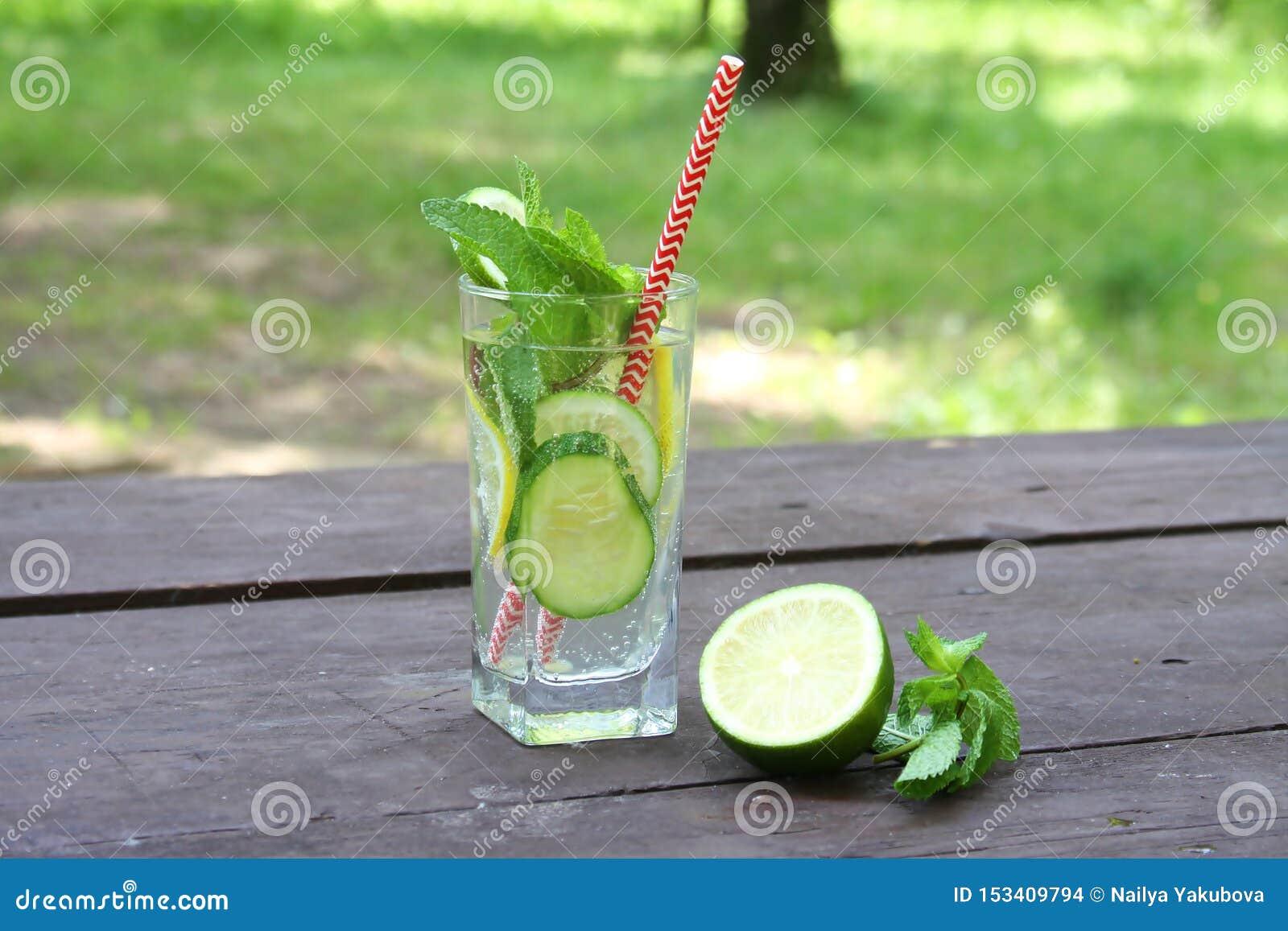 Освежая вода холодных напитков лета Sassy с лимоном, известкой, огурцом, мятой, имбирем в стекле на деревянном столе, на открытом