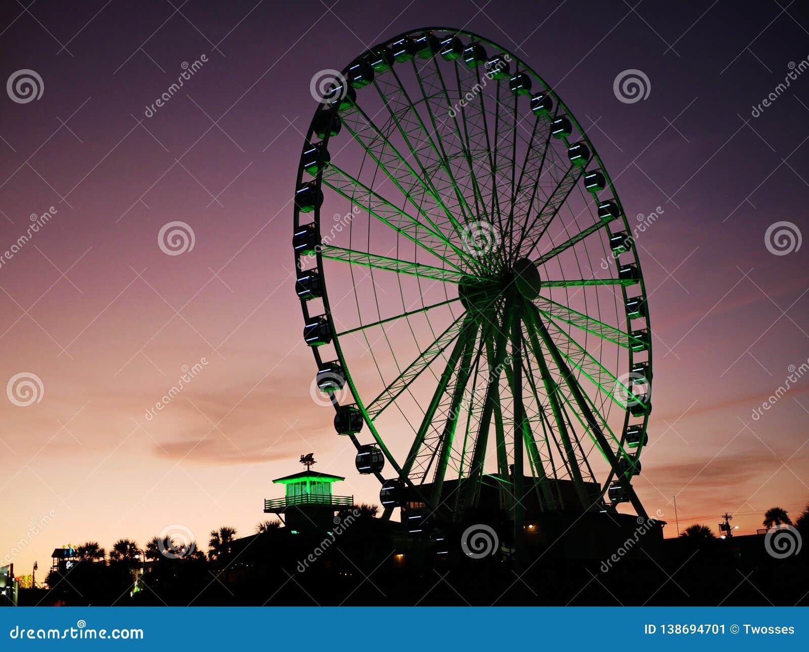 Освещенное колесо Ferris на пляже на сумраке