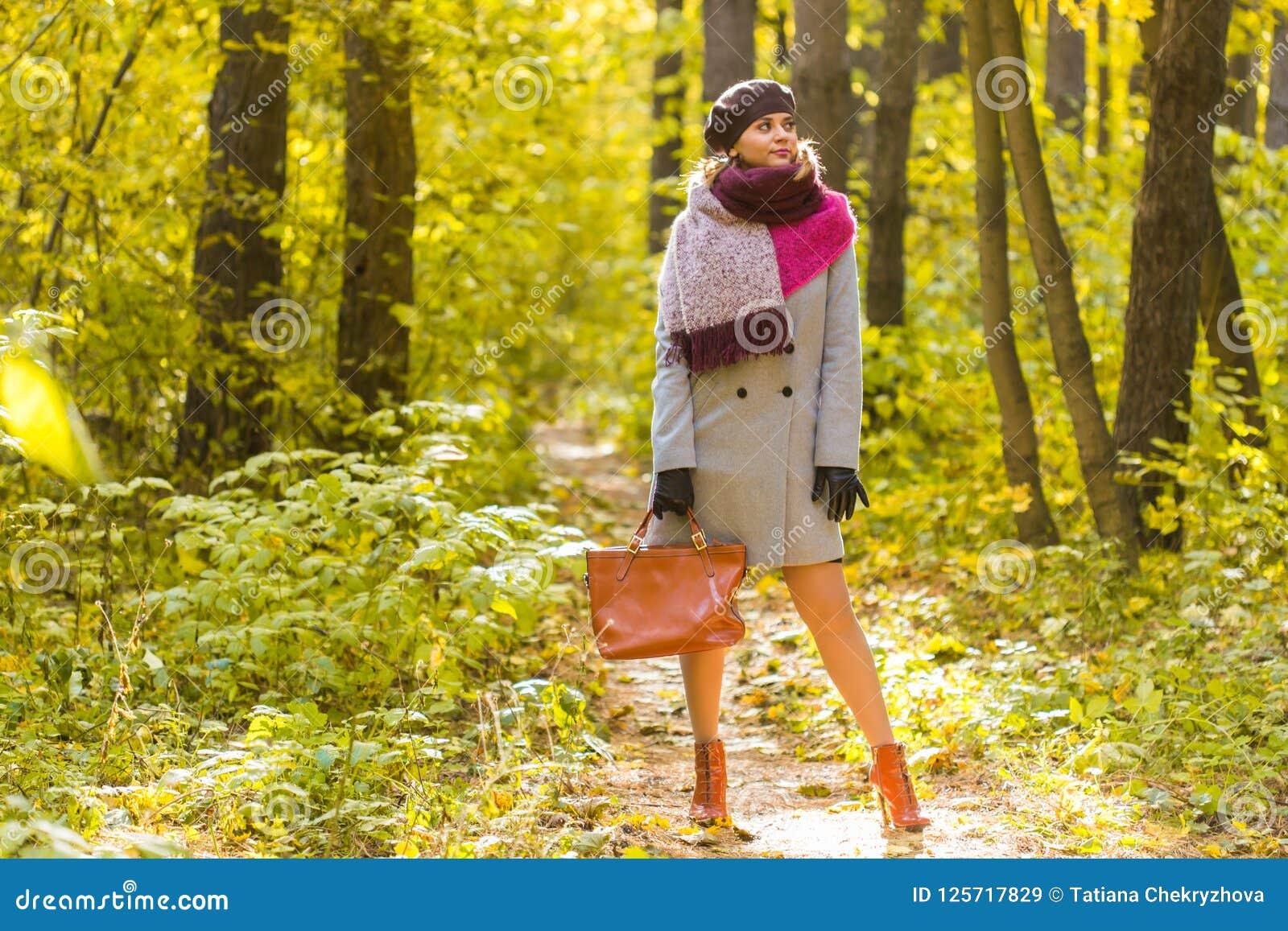 Осень, сезон и концепция людей - женщина в пальто при коричневая сумка стоя в парке осени