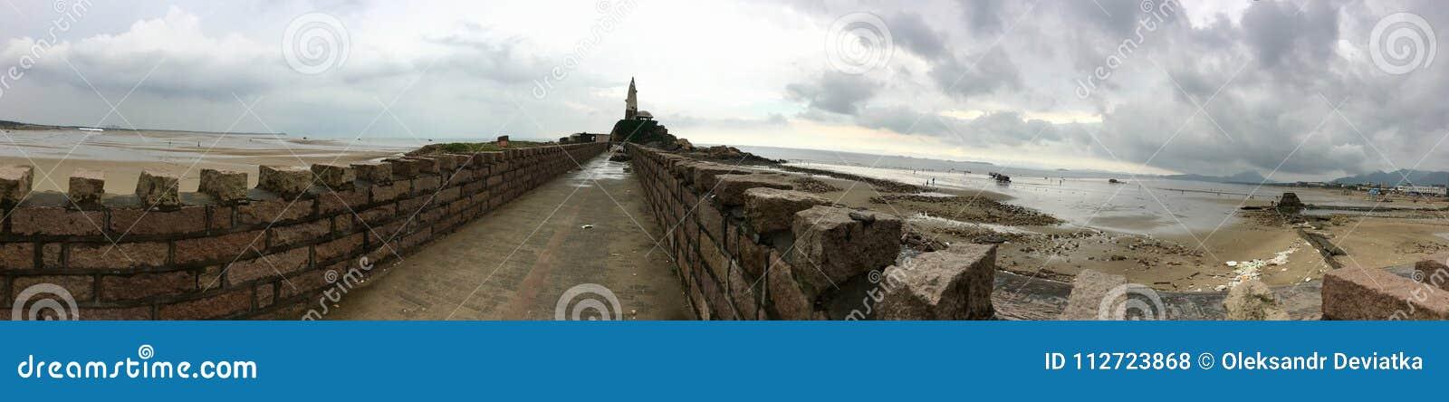 Осмотрите панораму старая каменная стена к маяку в море в Китае Ландшафт моря утра на пасмурный дождливый день