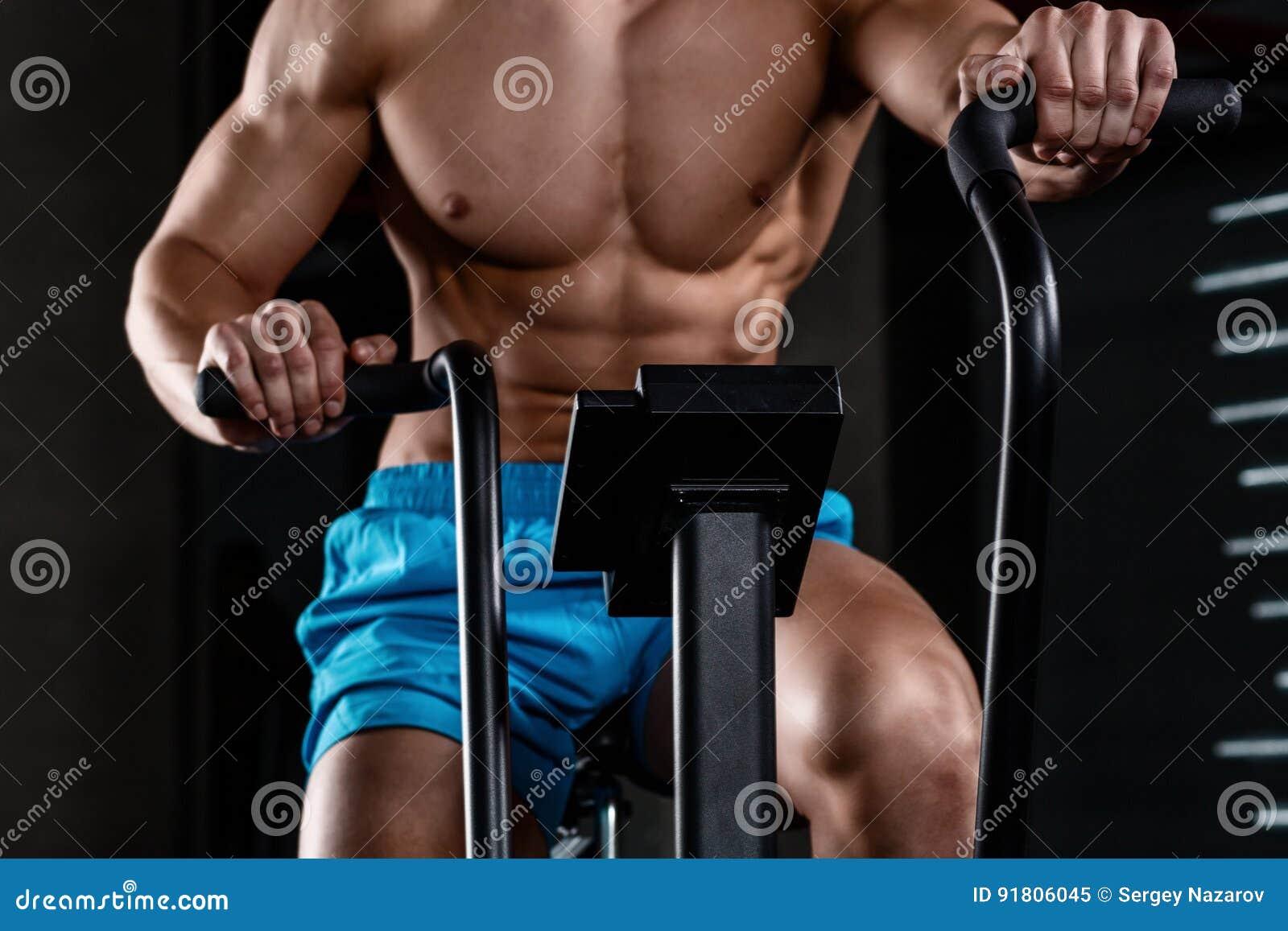 Осмотрите часть конца-вверх молодого человека в шортах спорт задействуя на спортзале