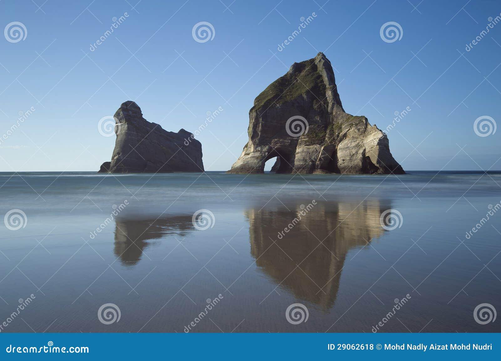 Острова аркы приближают к пляжу Wharariki, Новой Зеландии