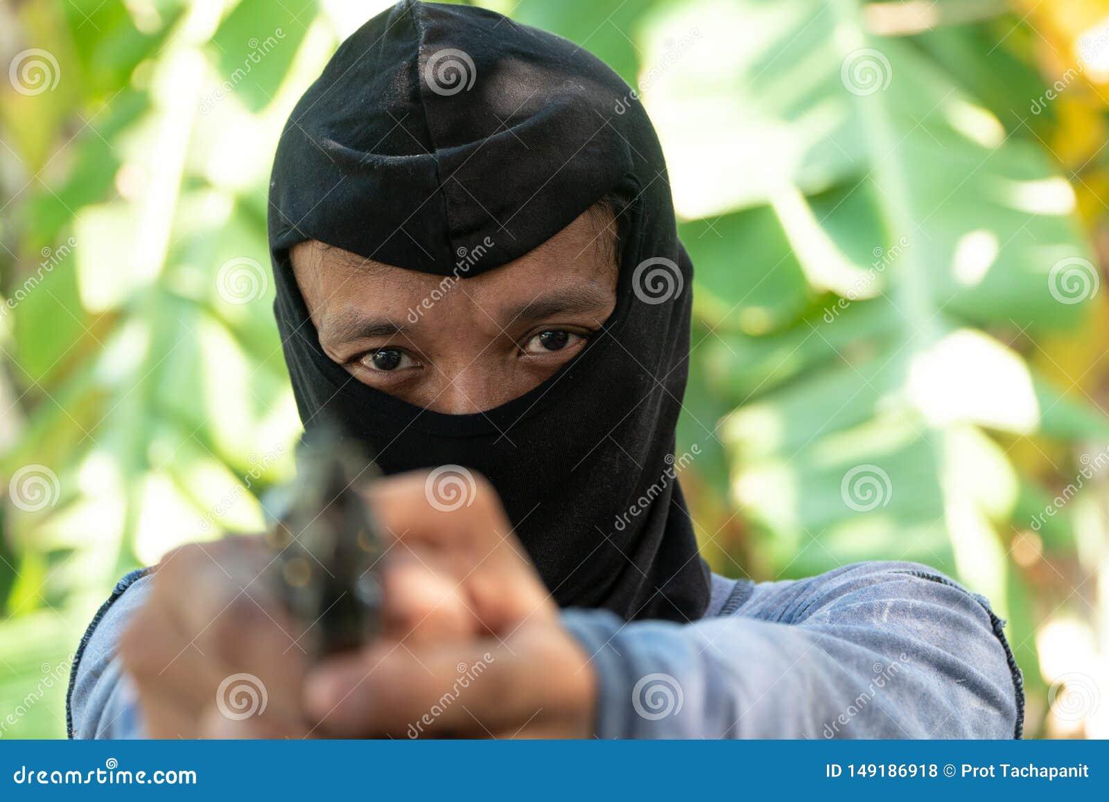 Отборный фокус глаз преступления Разбойник в черных целях лыжной маски с оружием