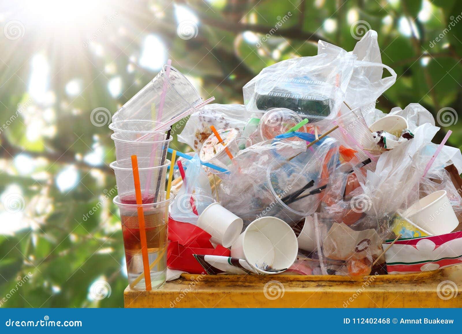 Отброс много конец-вверх на погани вполне мусорного ведра, серий полиэтиленового пакета ненужных старья на предпосылке солнечност