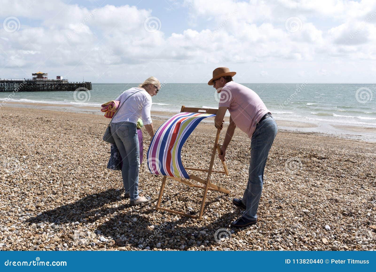 Отдыхающие раскрывая deckchair на пляже