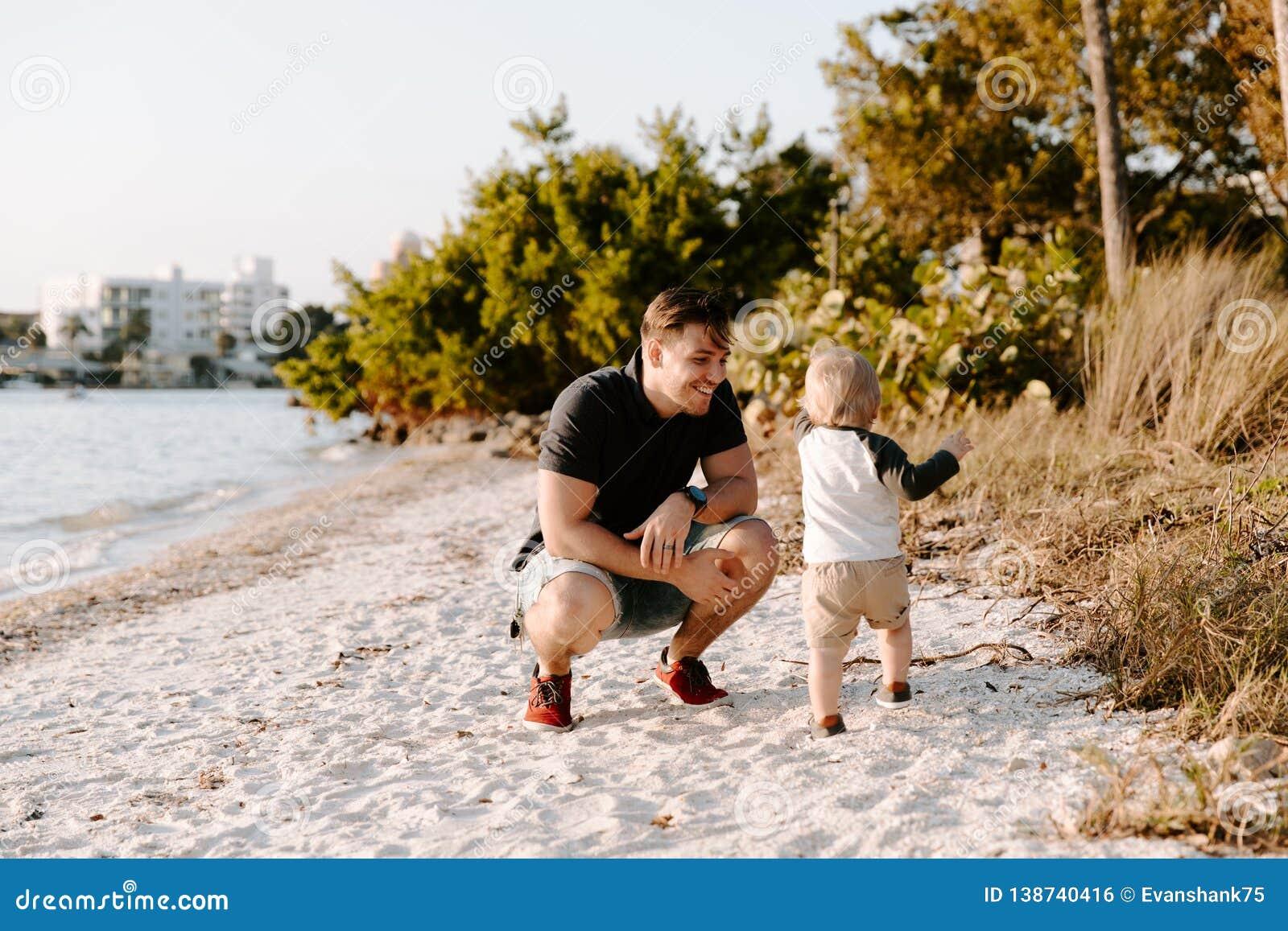 Отец детенышей и его милый сын мальчика идя и наслаждаясь славная на открытом воздухе погода на песчаном пляже рядом с заливом ок