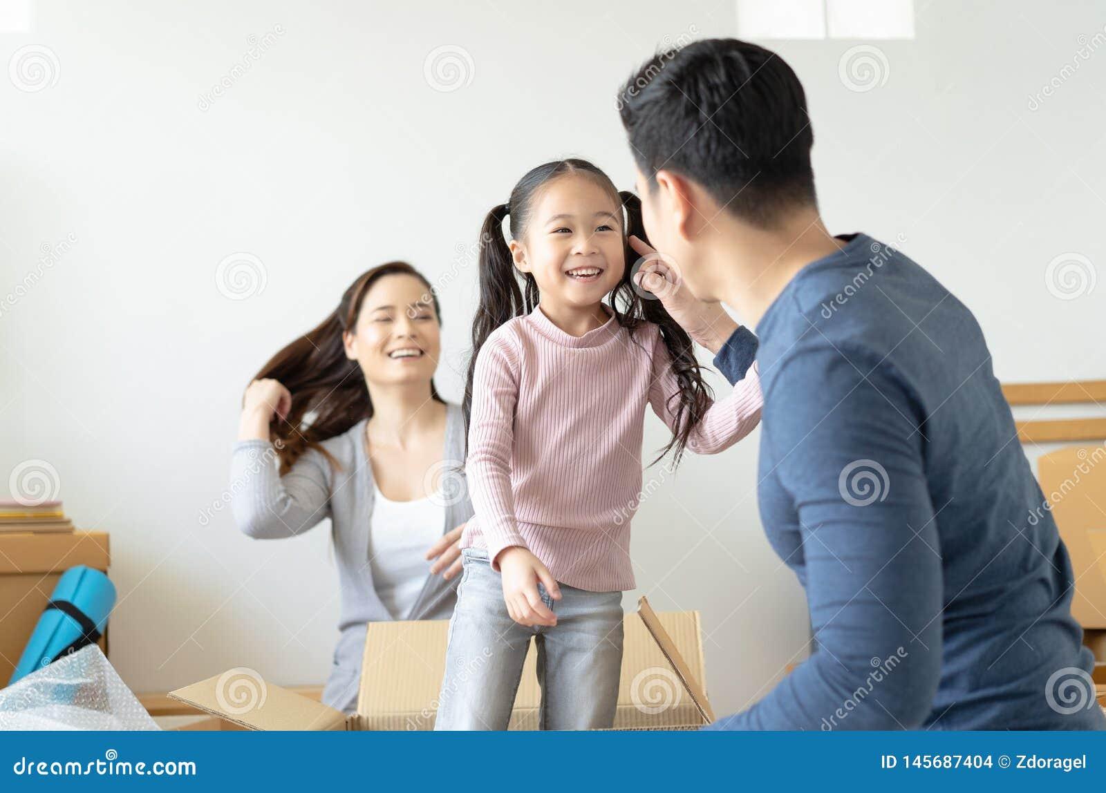 Отец играя милую маленькую дочь делая катание в картонных коробках, молодых азиатских детях семьи имея потеху в комнате прожития