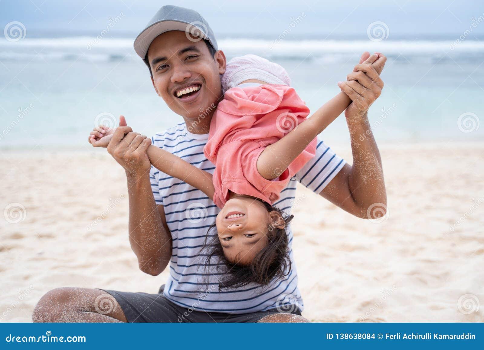 Отец играя с его прыжком кувырком дочери с главным положением дальше ниже