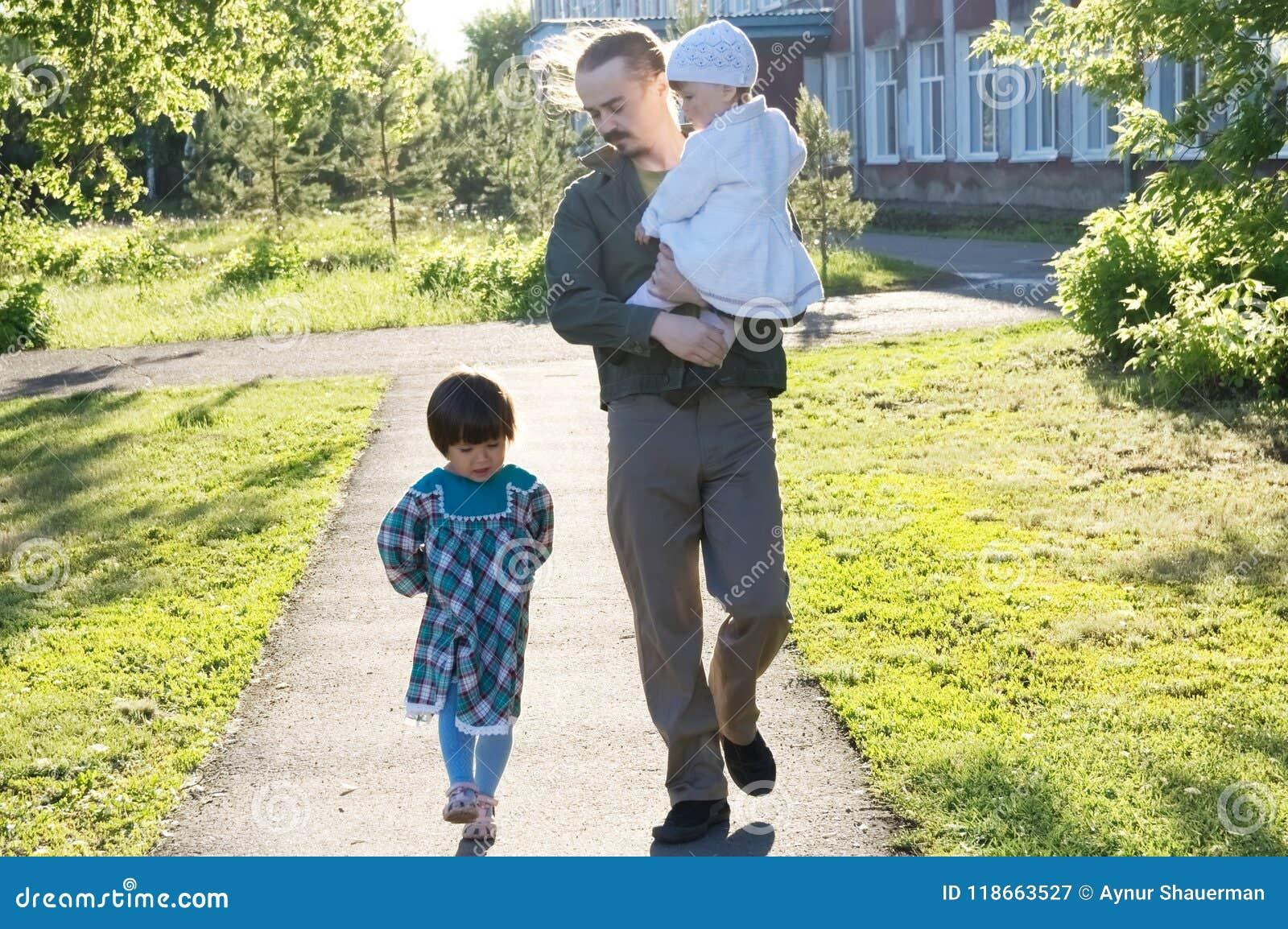 Отец идя с дочерьми на солнечном дне папа и девушки скрепляя отношение счастливый папа с 2 маленькими ребеятами в парке внешнем