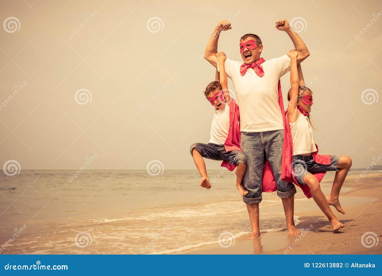 Отец и дети играя супергероя на пляже на ti дня