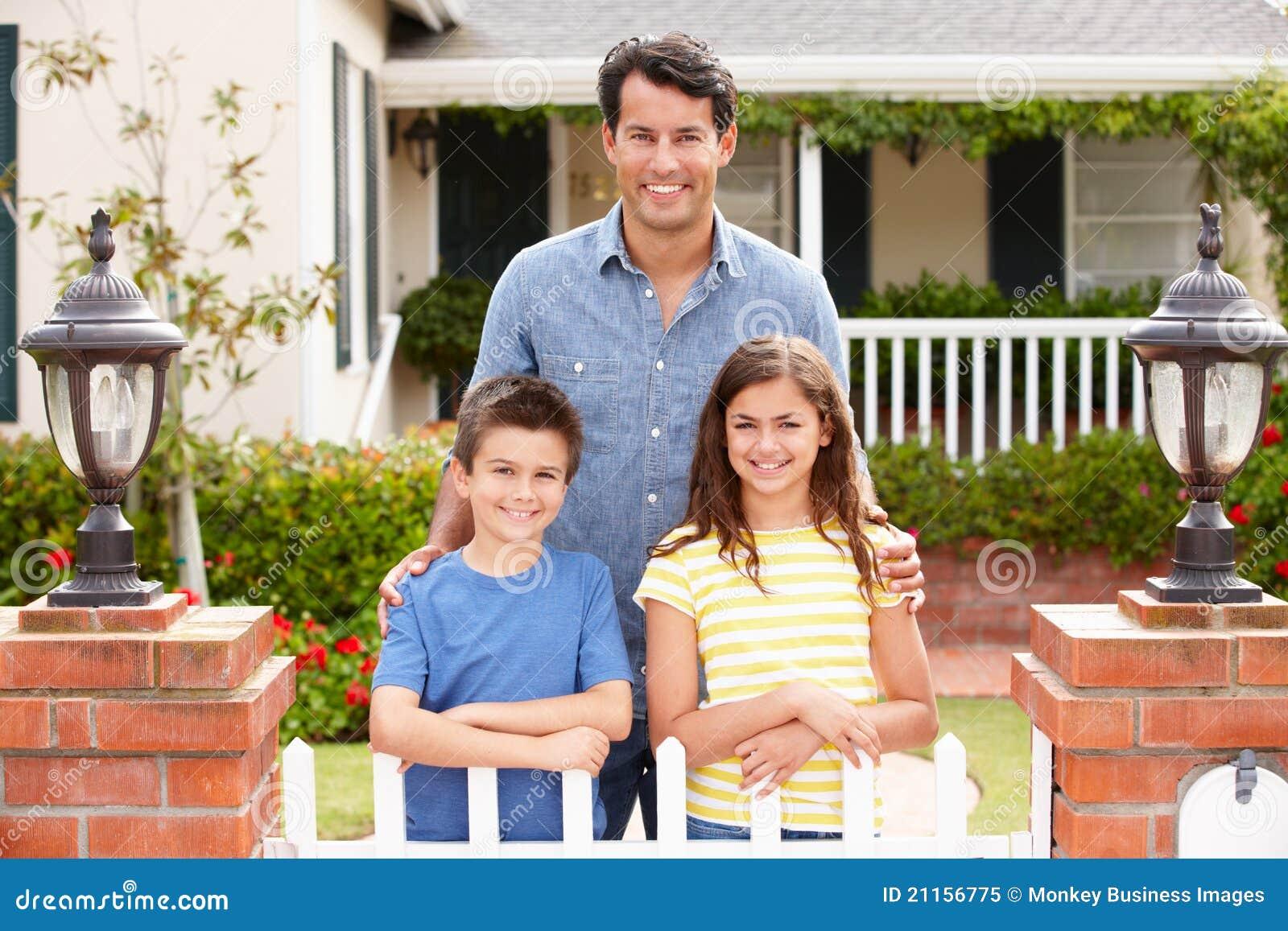 Отец и дети стоя внешний дом