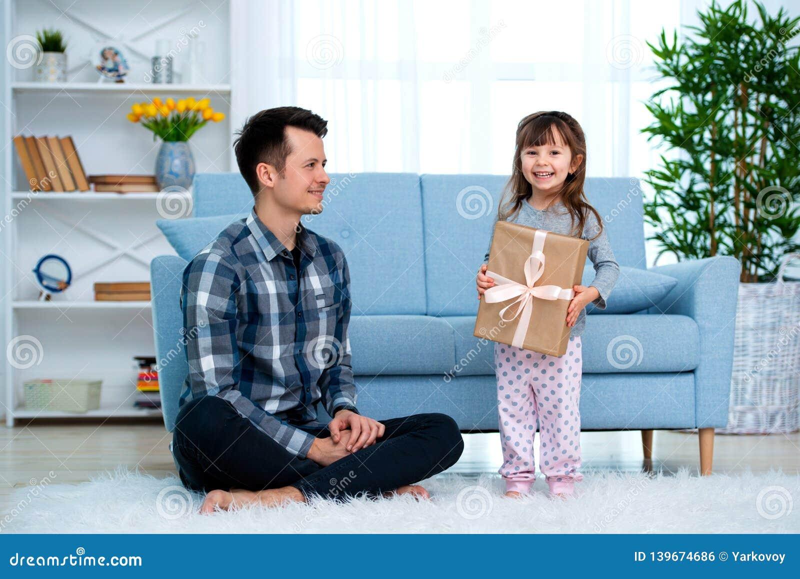 Отец и дочь или брат и сестра с подарком в интерьере комнаты Концепция праздника Дня отца, день детей