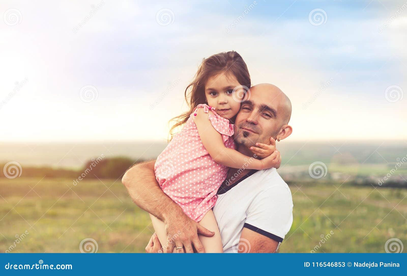 Отец и дочь обнимая на заходе солнца лета