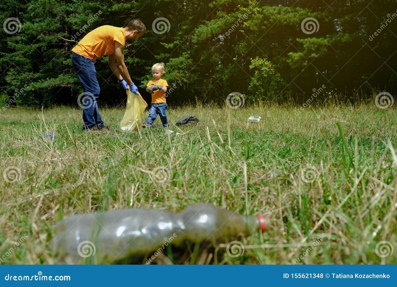 Отец и его маленький сын собирая отброс и пластиковые бутылки в парке Семья волонтеров комплектуя вверх сор в лесе