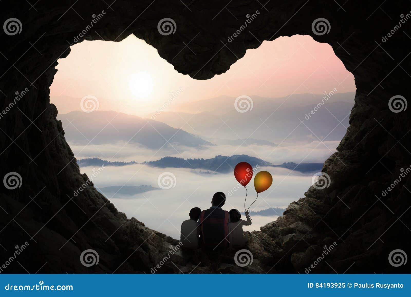 Отец и дети наслаждаются горным видом в пещере
