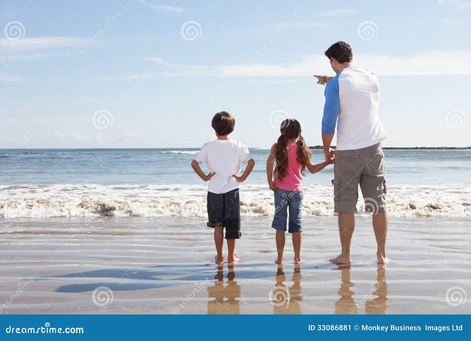 Отец и дети смотря к морю от пляжа