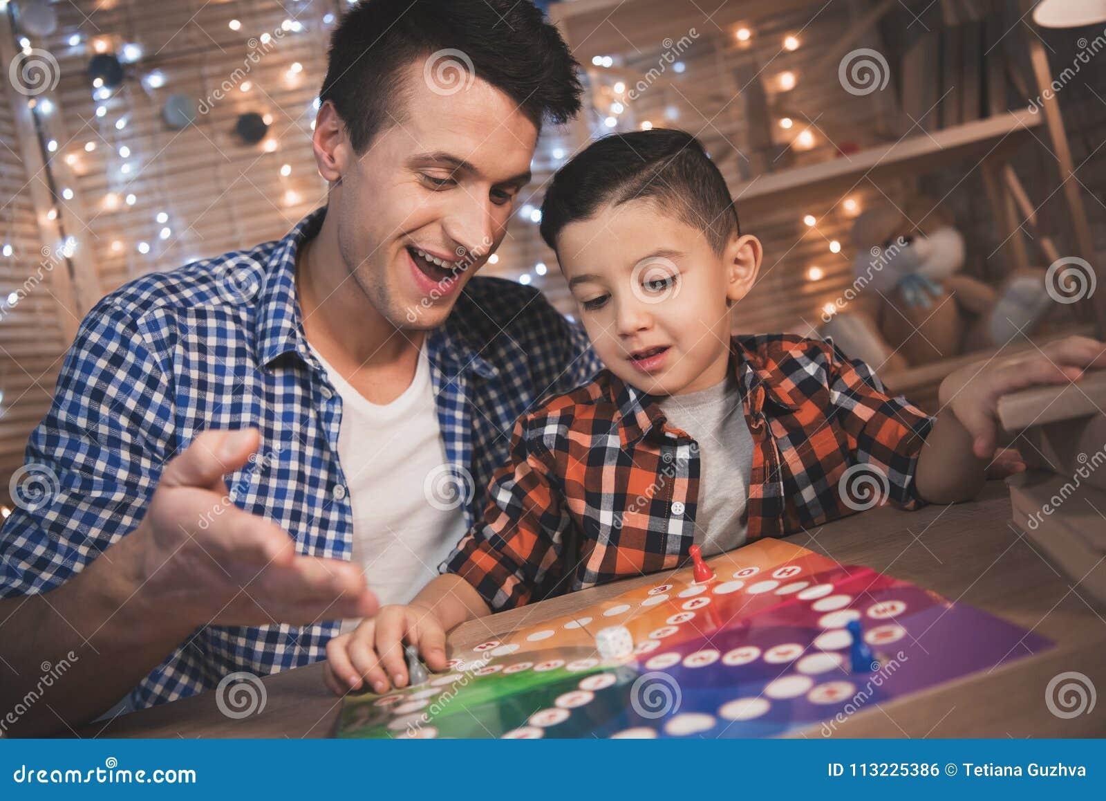 Отец и маленький сын играют настольную игру на ноче дома