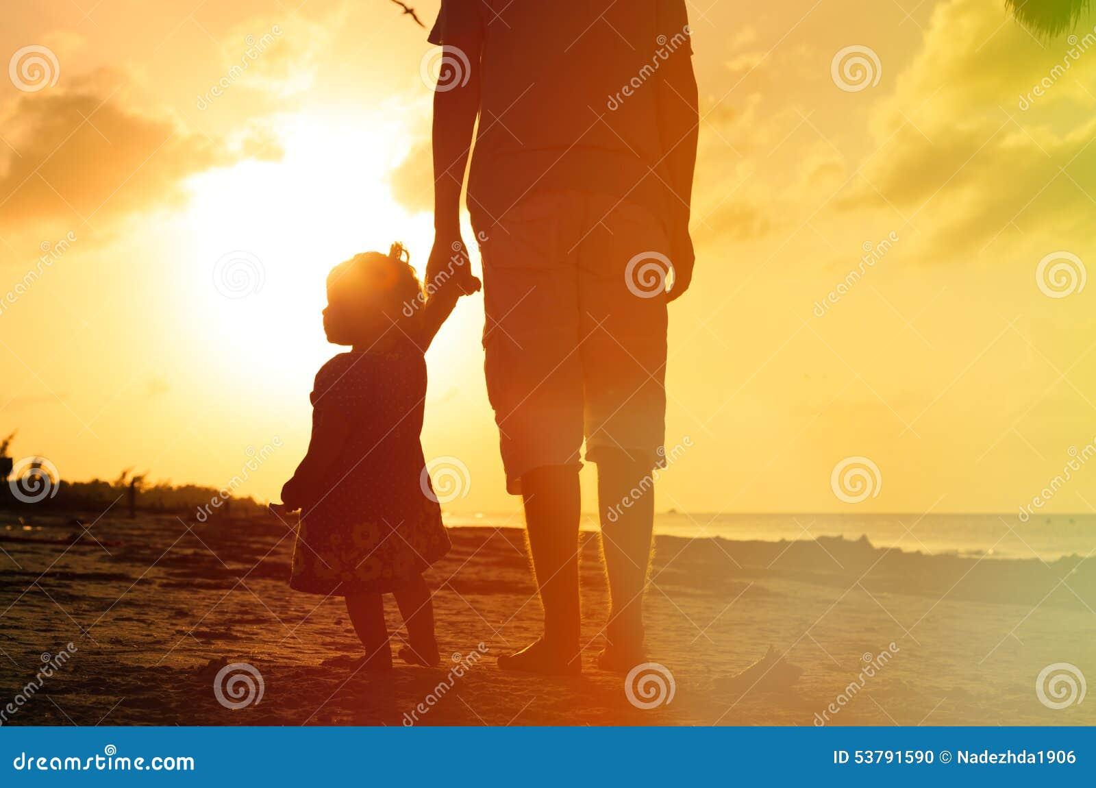 Отец и маленькая дочь идя на пляж на
