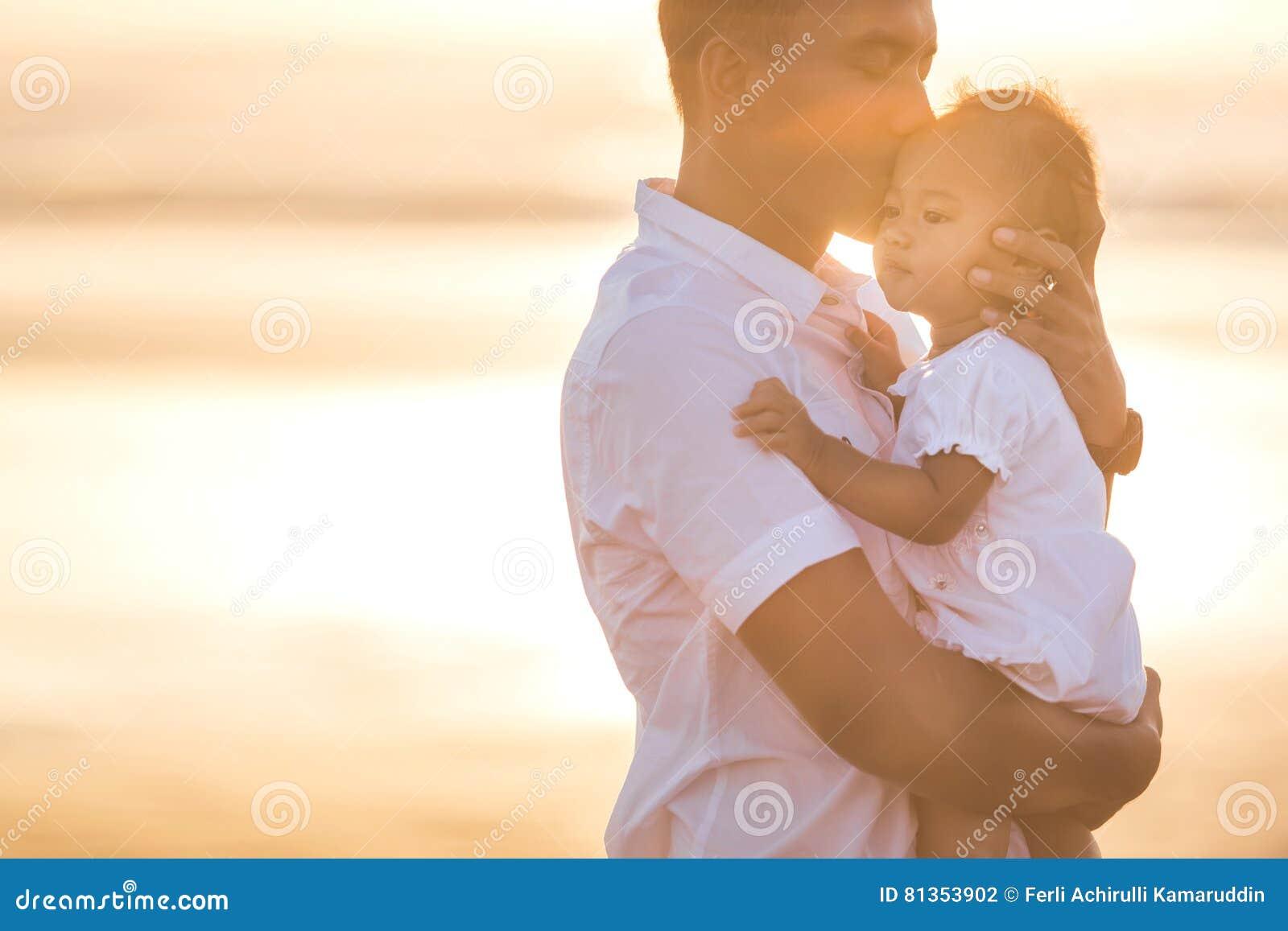 Отец и маленькая дочь младенца на пляже на заходе солнца