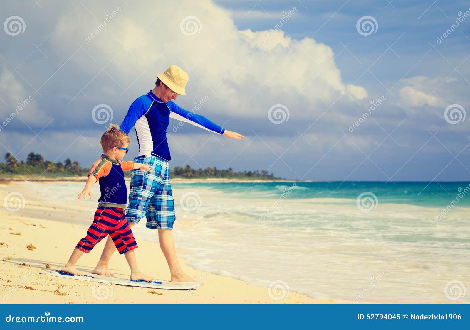 Отец и маленький сын практикуя занимающся серфингом positin
