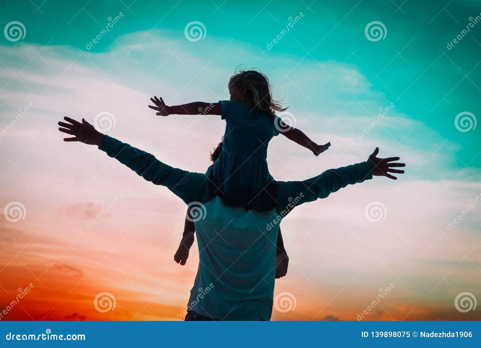 Отец и меньшая игра дочери на небе захода солнца
