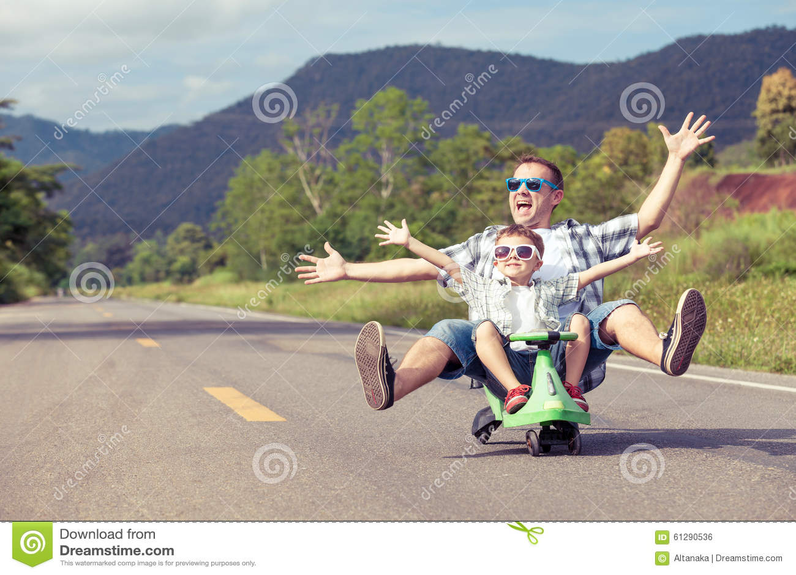 Отец и сын играя на дороге