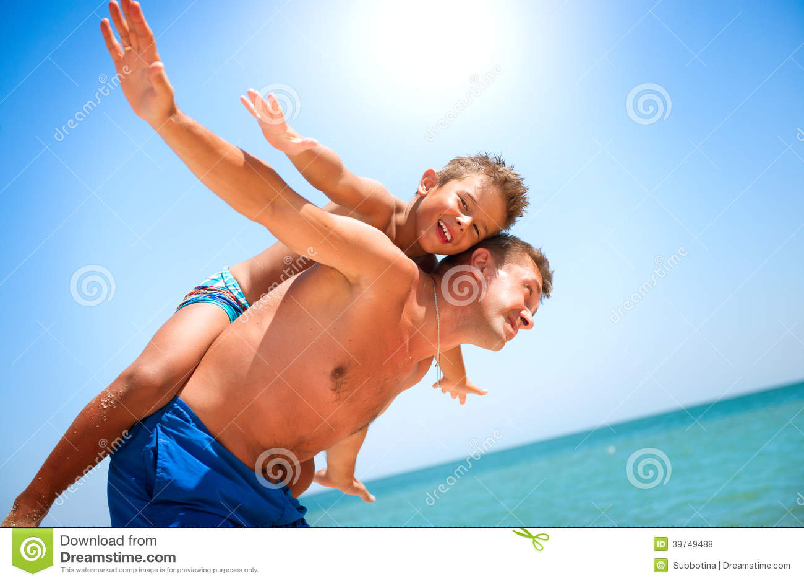 Отец и сын имея потеху на пляже