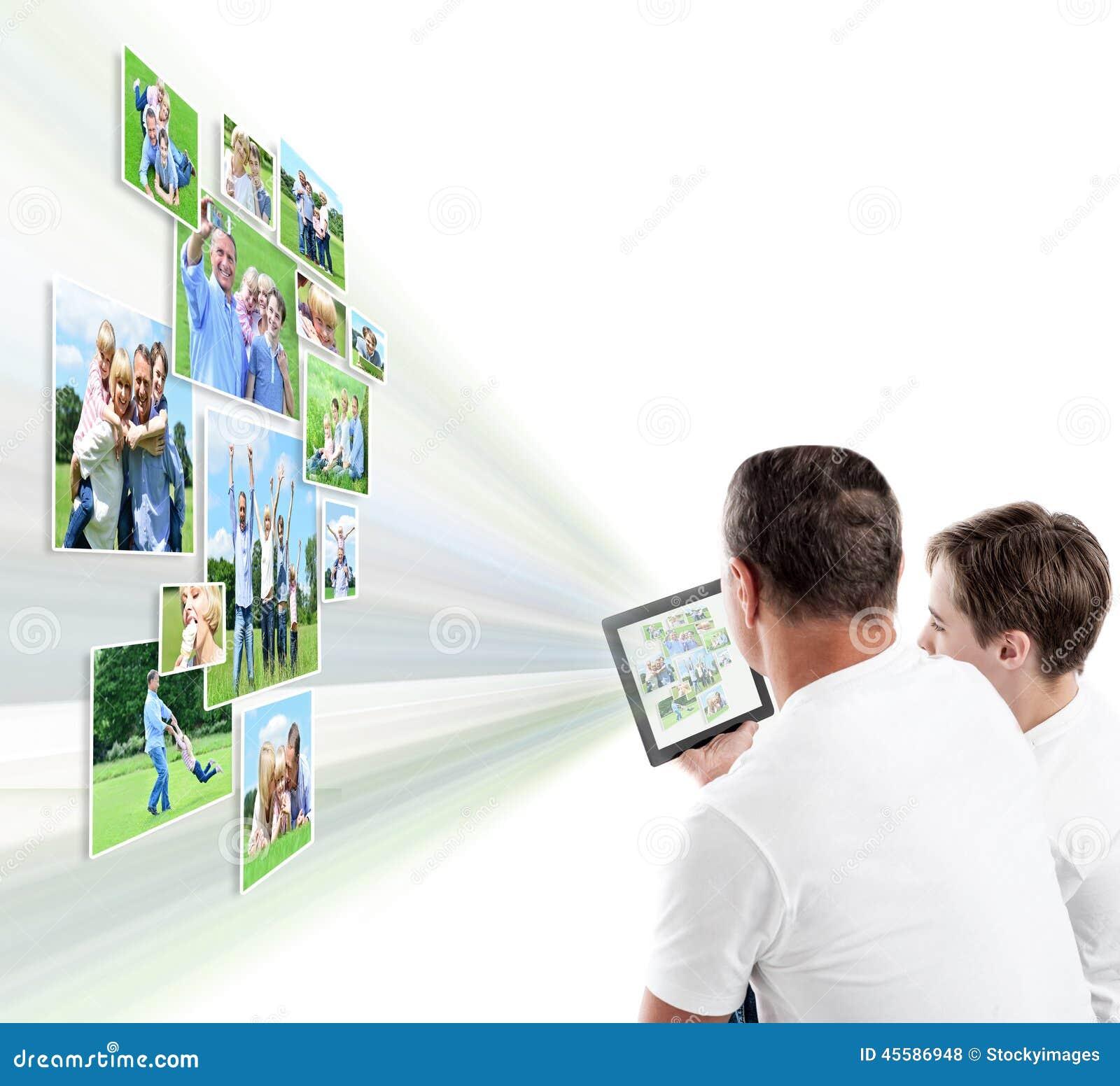 Отец и сын смотря изображения на таблетке