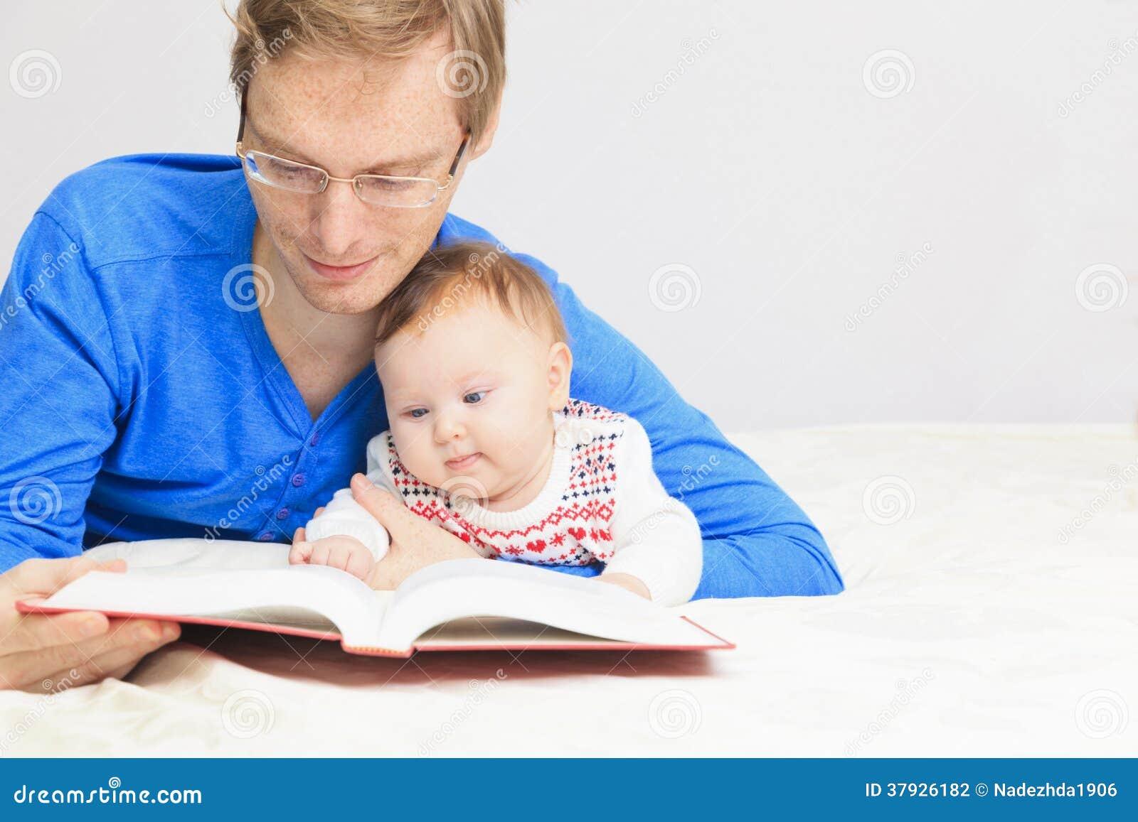 Отец при маленькая дочь читая дома