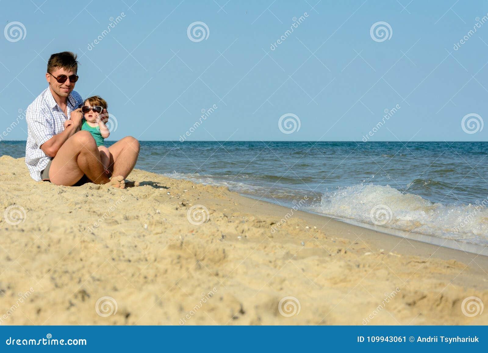 Отец с маленькой дочерью сидит на пляже на предпосылке моря