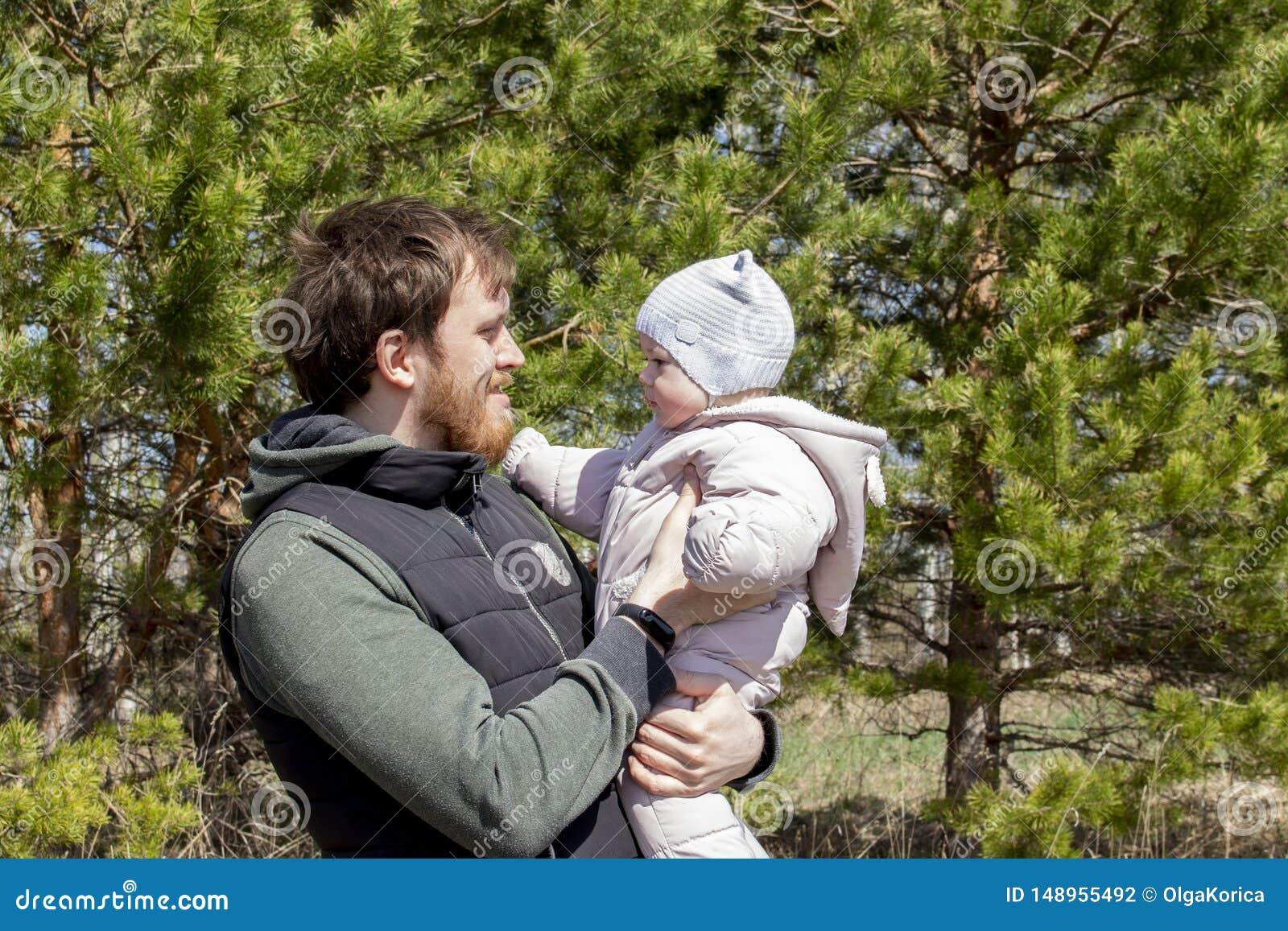 Отец с младенцем в его оружиях идет в парк Молодой человек с бородой держит девушку ребенка 9 месяцев
