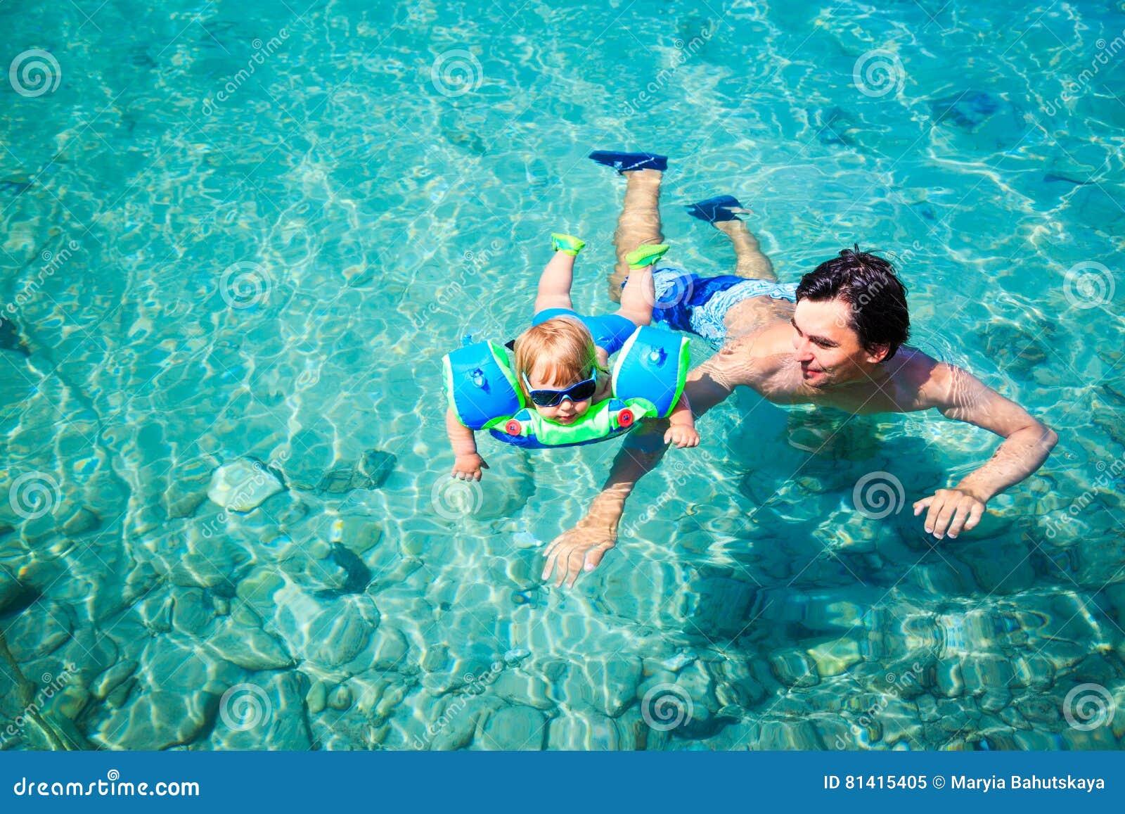 Отец учит, что его маленький сын плавает в море