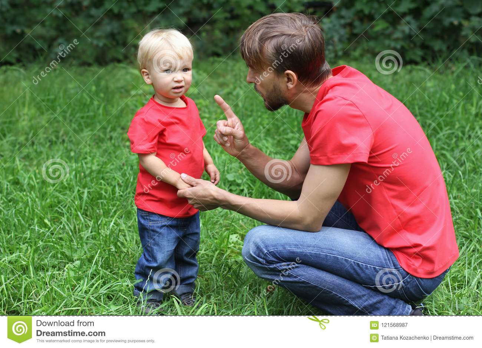 Отец эмоционально разговаривает с разочарованным ребенком Расстроенный малыш и его папа Концепция затруднений воспитания Одежда в